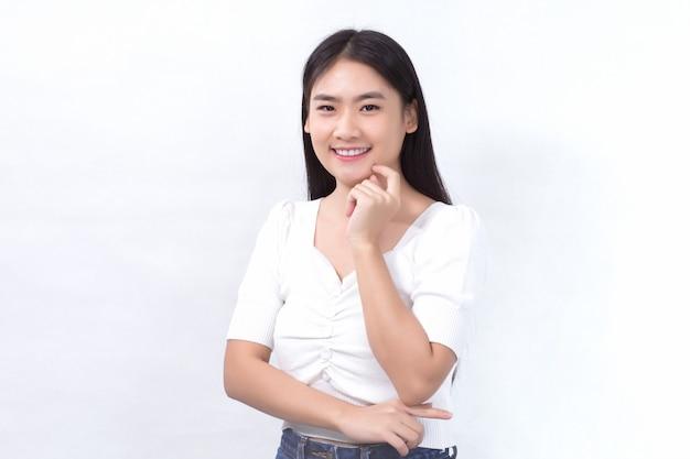 白いシャツを着た肖像画アジアの美しい少女は、白い背景のスタジオで彼女の顔と笑顔に触れます。