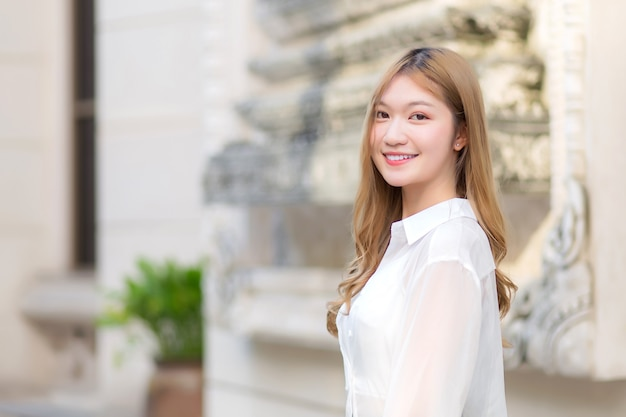Portrait asian beautiful girl with long bronze hair in white long sleeve shirt stand smile in an urban outdoor park.