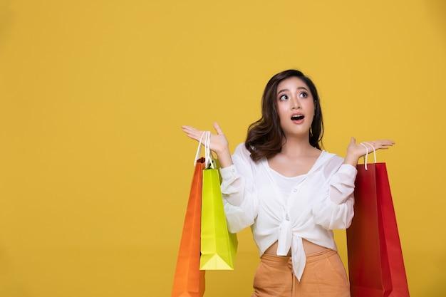 陽気な笑顔と黄色のスタジオの背景に分離された買い物袋を保持しているアジアの美しい幸せな若い女性の肖像画。幸福、消費、販売、人々の買い物の概念