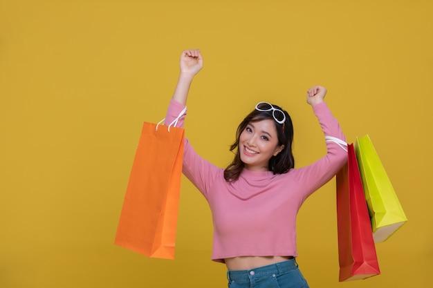 陽気な笑顔と黄色に分離された買い物袋を保持している肖像画アジアの美しい幸せな若い女