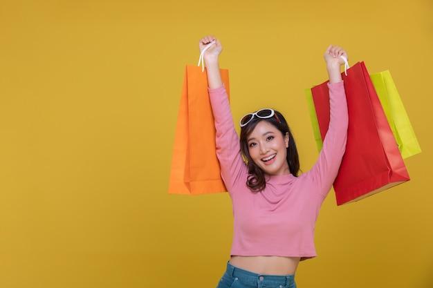 陽気な笑顔と分離された買い物袋を保持している肖像画アジアの美しい幸せな若い女