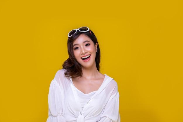 Портрет азиатской красивой счастливой молодой женщины, улыбающейся веселой и смотрящей в камеру, изолированную на желтом студийном фоне