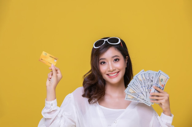 肖像画アジアの美しい幸せな若い女性陽気な笑顔と彼女はクレジットカードを持っています
