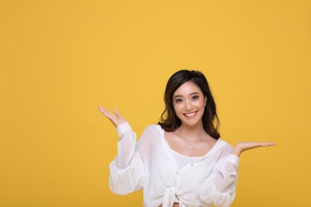 노란 스튜디오 배경에 격리된 밝은 미소를 짓고 있는 아시아의 아름다운 행복한 젊은 여성