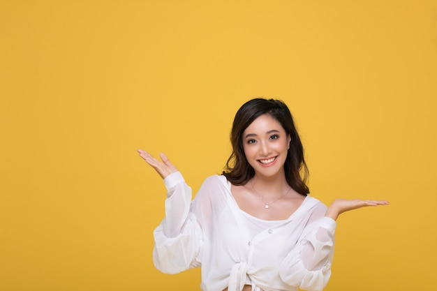Portrait asian beautiful happy young woman smiling cheerful  isolated on yellow studio background