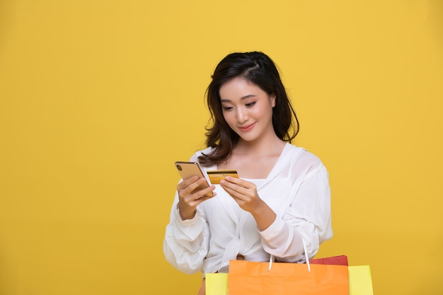 Portrait asian beautiful happy young woman smiling cheerful and she is holding credit card and using smartphone for shopping online with shopping bags isolated on yellow studio background.