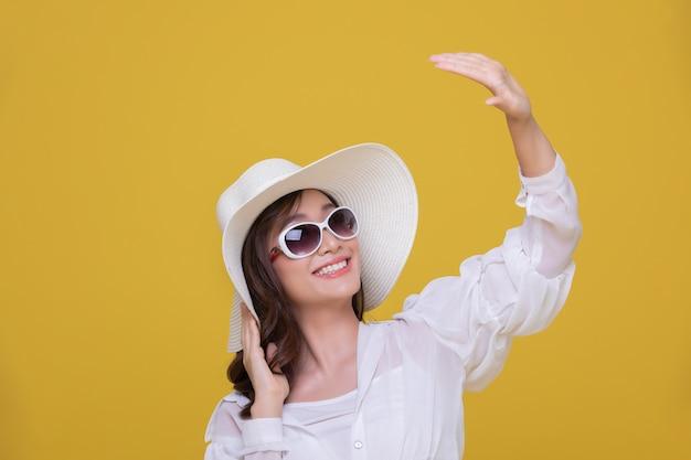 肖像画サングラスと帽子笑顔の陽気な笑顔で美しい幸せな若い女