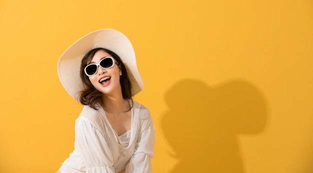 Portrait asian beautiful happy young woman with sunglasses and hat smiling cheerful in summer and looking at camera isolated on yellow studio background.