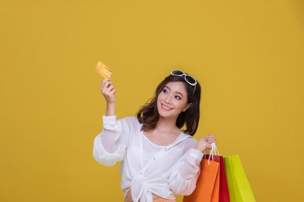肖像画アジアの陽気な笑顔のサングラスをかけた美しい幸せな若い女と彼女はクレジットカードを持っています