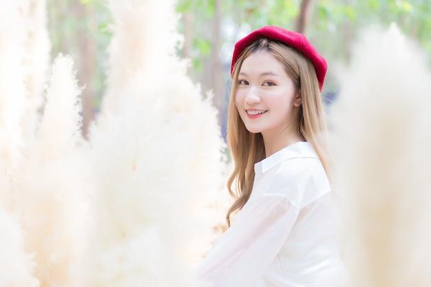 色の乾いた草で白いドレスと赤い帽子の笑顔を着ている肖像画アジアの美しい女性