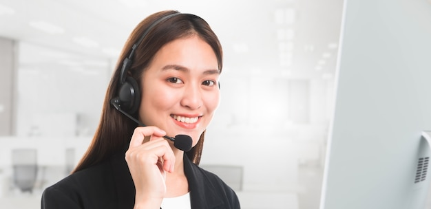 Portrait of asian beautiful smiling woman customer support phone operator in office backgr