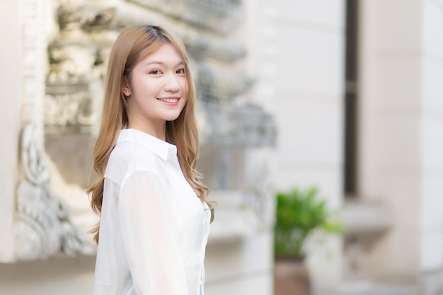 Portrait asian beautiful woman with long bronze hair in white long sleeve shirt stand smile in an urban outdoor park.