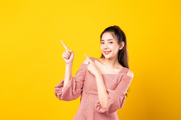 Portrait of asian beautiful young girl pointing fingers with both hands aside