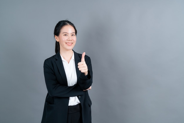 立っている肖像画アジアの美しい若い女性、彼女は灰色の壁に指の親指を立てた