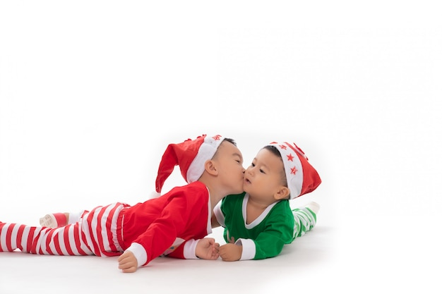 Portrait asian boy kisses his happy brother on white