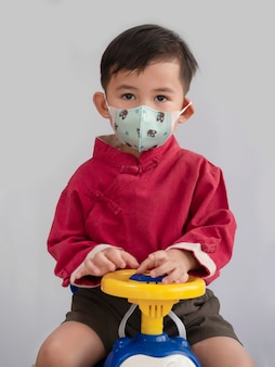 Portrait of asian boy wearing mask on a toy car