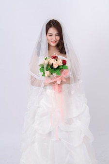 Portrait of asian bride wearing the white dress on the white.