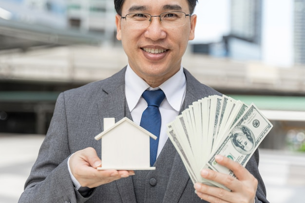 Portrait asian business man holding money us dollar bills and model house on business district