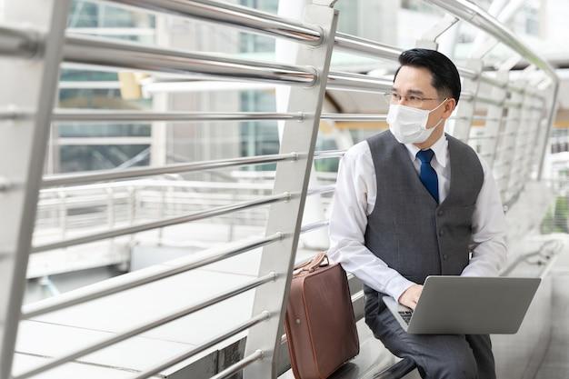 격리 기간 동안 보호를 위해 보호 얼굴 마스크를 쓰고 세로 아시아 비즈니스 남자