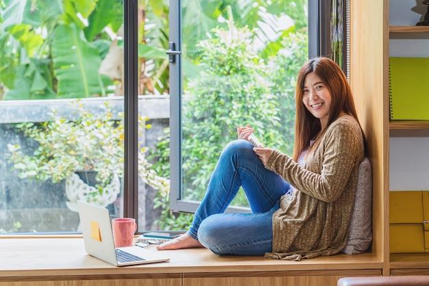 屋内のモダンな家でテクノロジーラップトップを使用して作業し、使用している肖像画アジアのビジネスウーマン