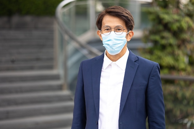 Portrait asian businessman wearin protective face mask prevent covid-19 virus  standing outdoor in the city.