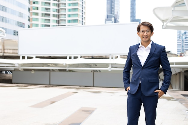 Portrait asian businessman wearing suit jacket standing outdoor in the city. empty banner for text background.