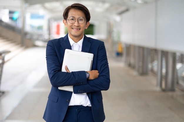 Portrait asian businessman wearing suit jacket walking go to work in morning outdoor.