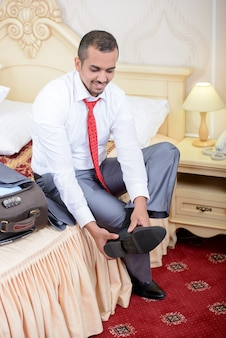 Portrait of asian businessman with suitcase, sitting on bed.