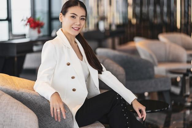 Портрет азиатской бизнес-леди в строгом костюме, сидя на диване в современном вестибюле