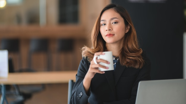 Portrait of asian businesswoman working on her project and drinking a coffee while looking at the camera