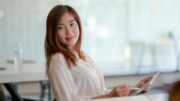 Portrait of asian businesswoman working on her project and smiling to the camera