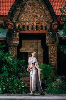 Portrait asian charming woman wearing beautiful typical thai dress in ancient temple or famous place with gracefully pose