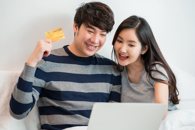 Portrait of a asian cheerful couple shopping online on internet with laptop computer while sitting at on the bed at home