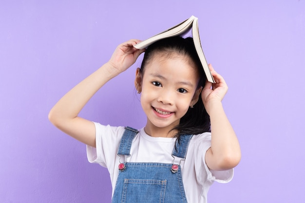 Portrait of asian child holding book on purple background