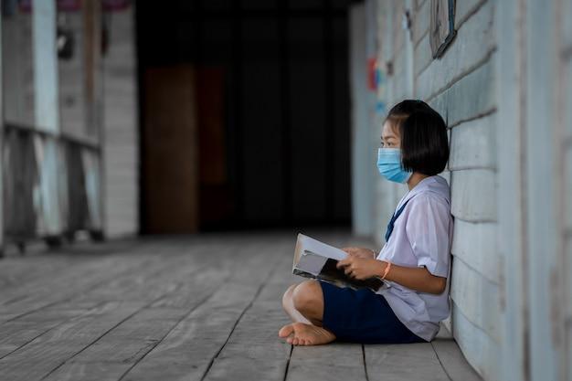 Студент портрета азиатских детей носит лицевую маску, сидя в начальной школе.