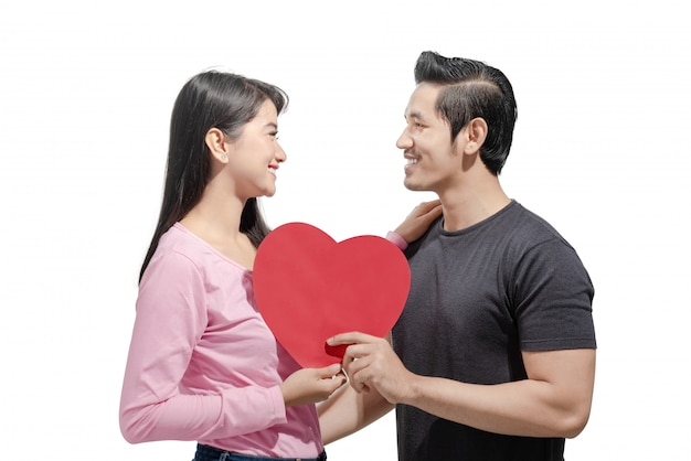 Portrait of asian couple holding red heart and looking at one another