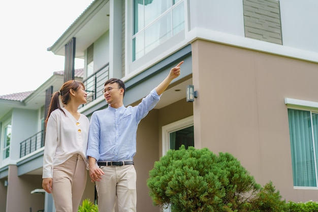 Portrait of asian couple walking and hugging together looking happy in front of their new house to start new life. family, age, home, real estate and people concept.