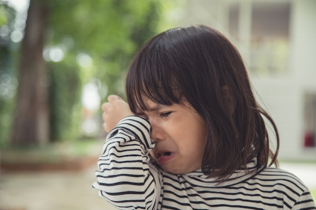 Portrait of asian crying little girl with little rolling tears weeping emotion, hurt in pain fit drops cheek. young crying panic drama asian toddler.