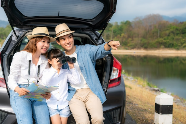 Portrait of asian family sitting in car with father pointing to view and mother holding maps with daughter looking beautiful landscape through binoculars while vacation together in holiday.