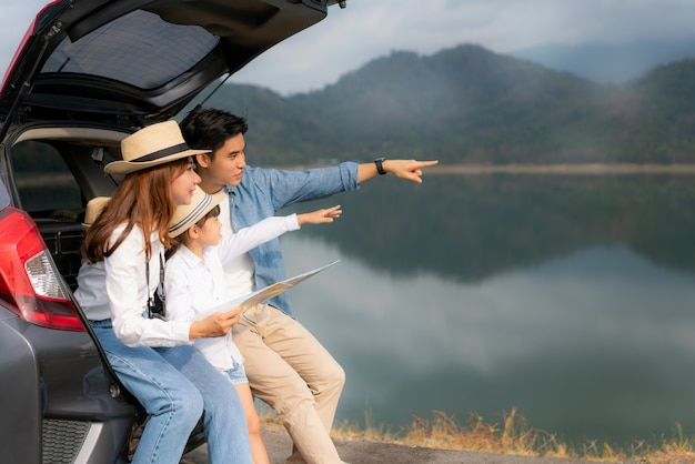 Portrait of asian family sitting in car with father pointing to view and mother with daughter looking beautiful landscape and holding maps while vacation together in holiday. happy family time.