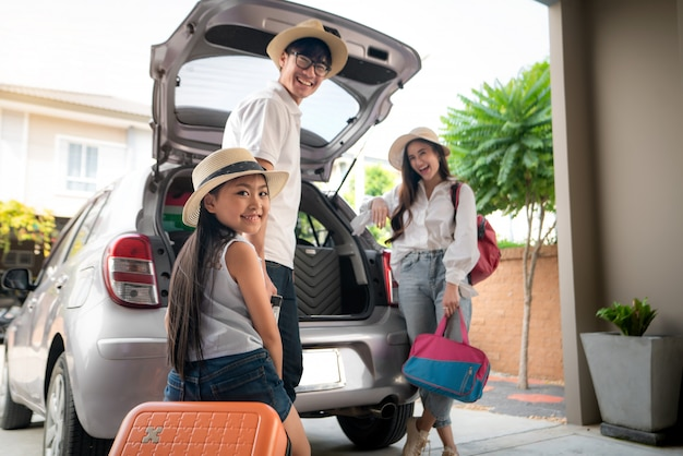 Portrait of asian family with father, mother and daughter looks happy while preparing suitcase into a car for holiday.