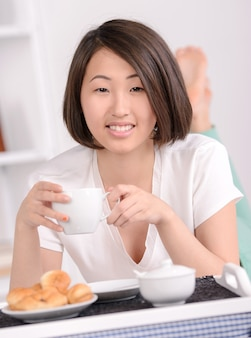 Portrait of asian female lying on bed and eating breakfast.