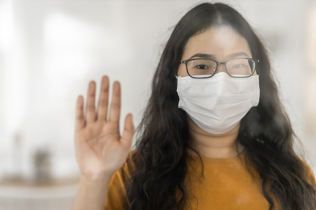 Portrait of asian female wears hygiene protective mask in orange dress doing a stop gesture with protective gloves in hands while looking at camera in the consultation,concept of covid-19 virus
