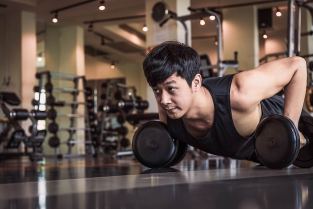 Portrait of asian fitness man doing pushing up exercise with dumbbell in gym.