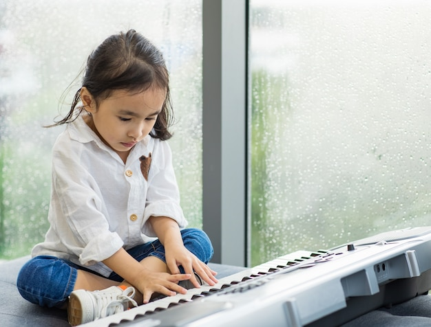 Portrait asian girl child look adorable and very cute playing music electronic keyboard feel casual and relaxation in home.