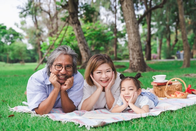 Portrait of asian grandparents and granddaughter laying on the green glass field outdoor, family enjoying picnic together in summer day concept