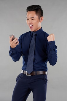 Portrait of asian guy in smart clothes excited by smartphone news against grey background