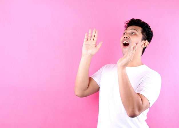 Portrait of asian guy yelling and hand on his mouth, on pink wall copy space.