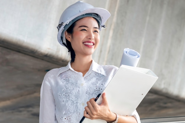 Portrait of asian happy woman engineer holding blueprint and wearing white safety helmet at outdoor.
