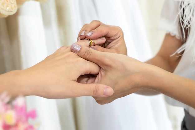 Portrait of asian homosexual couple puts on a wedding ring. concept lgbt lesbian.